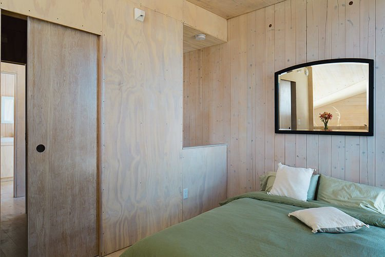 The bedroom is outfitted with only the basics. Tagged: Bedroom, Bed, and Wall Lighting.  Sky House by Dwell