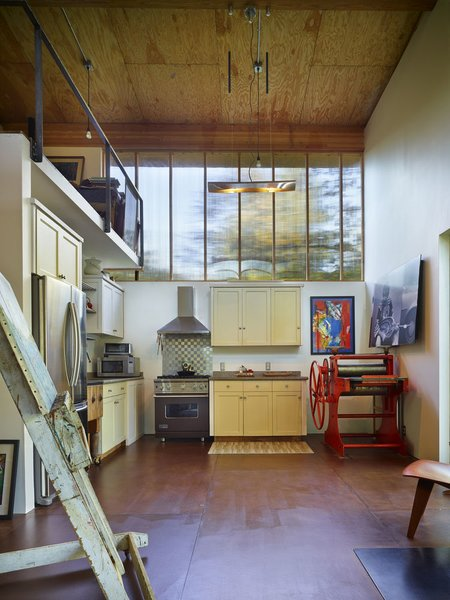 The kitchen and living area occupies the ground level of the double-height interior while a sleeping loft is above.  Photo 7 of Scavenger Studio modern home