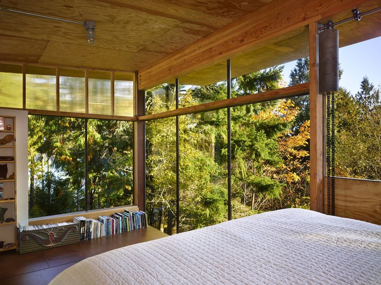 In the sleeping loft, floor-to-ceiling windows overlook the fir canopy of the surrounding forest.   Scavenger Studio by Dwell