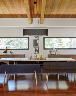 Pull Up a Chair in One of These 20 Modern Dining Rooms - Photo 16 of 20 - A wood slab table is paired with bench seats from De La Espada and a vintage brass candelabrum in a family home near Lake Tahoe. The credenzas are Bo Concept. An oversize oval black linen shade from Dogfork Lamp Arts hangs above a table Maca created out of a wood slab from West Marin-based artisan Evan Shively of Arborica. The brass candelabrum is vintage, sourced from 1stDibs.