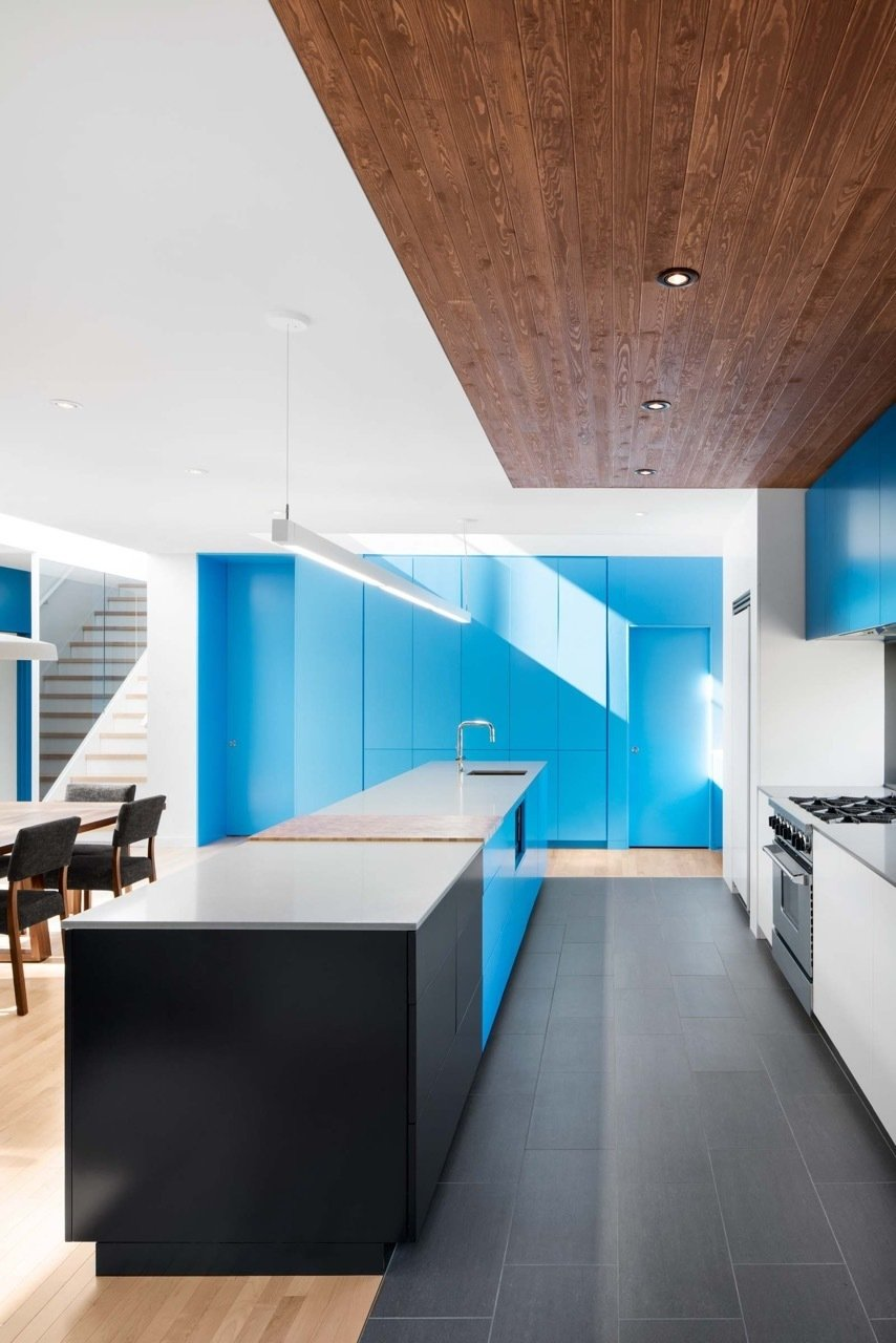 #interior #design #interiordesign #blue #kitchen #whitecountertop #countertop #woodfloor #black #stairs #woodtable #stove #woodceiling #lighting #kitchenlighting #storage #modern #stonegray #quartz #benjaminmoore #rockymountain #sky #quebec #renovation #naturehumaine #cabinets  36+ Interior Color Pop Ideas For Modern Homes by Dwell