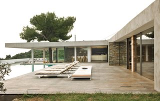 9 Modern Beach Bungalows - Photo 8 of 9 - Perched on the mountainside of the Greek island of Skiathos, this midcentury modern-inspired house by Athens-based K-Studio employs stone walls, pine trees, a deep overhang, outdoor rooms, a swimming pool, and endless views of the sea to great effect.