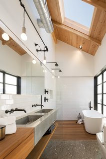 8 Spa-Like Bathrooms Designed to Instantly Soothe - Photo 5 of 8 - A skylight illuminates the neutral palette of this master bathroom, letting bathers peacefully contemplate the clouds from the privacy of its enclosed walls. The wood counter, concrete sink, and pebbled floor create a calming, textured space, and the natural materials stand out against the white subway tile.