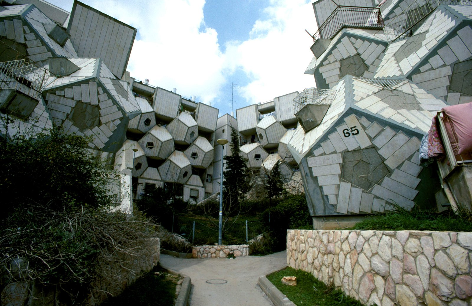 """Polish-born Israeli architect Zvi Hecker spent much of his career exploring cubes and dodecahedrons in his work. One of his most famous structures is the Ramot Polin housing project in Jerusalem erected for an ultra-orthodox population. The hivelike prefabricated building was lauded when it was completed in the 1970s. Over the years, people have adapted the structures and reports say that there isn't a single """"original"""" apartment left in the 700+ units.  Geometric Housing Complex in Jerusalem  by Diana Budds"""