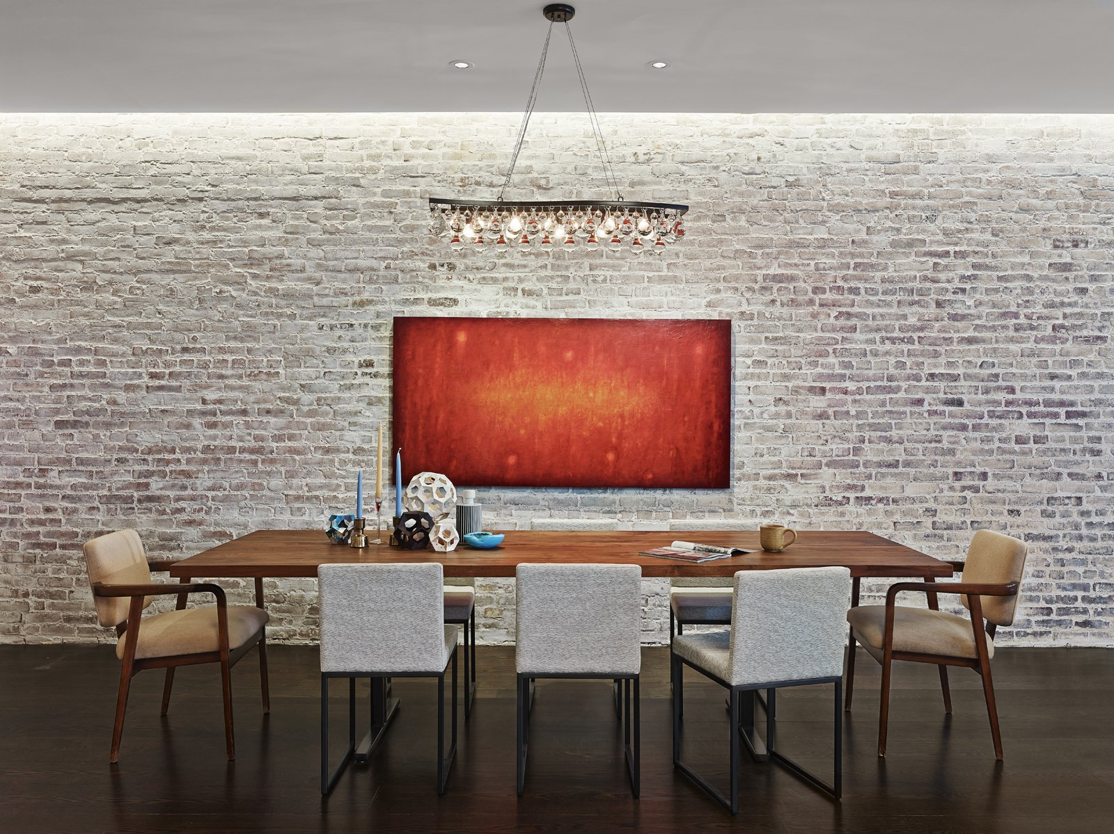 "The brick wall adjacent to the custom dining table by Brooklyn-based Uhuru Design is original to the structure. 590BC and its team spent months trying to find the right translucency for the whitewash covering the brick. ""We call it the 'selective loft' because of the contrast of the refined materials and cabinetry against the industrial materials of this former light bulb factory,"" says Breitner. Photo by Frank Oudeman."