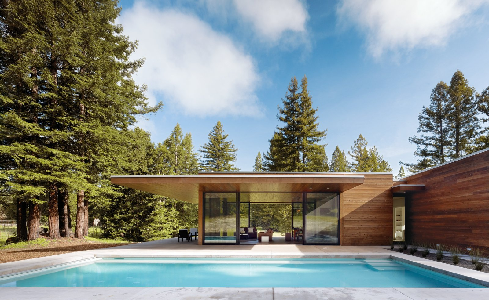 Two linked 1,000-square-foot pavilions are greater than a sum of their parts. The simply detailed, taut, flat-roofed home's two wings form a T-shape. One wing runs north to south, parallel to a pool, and contains the open-plan living spaces. Photo by Matthew Millman.