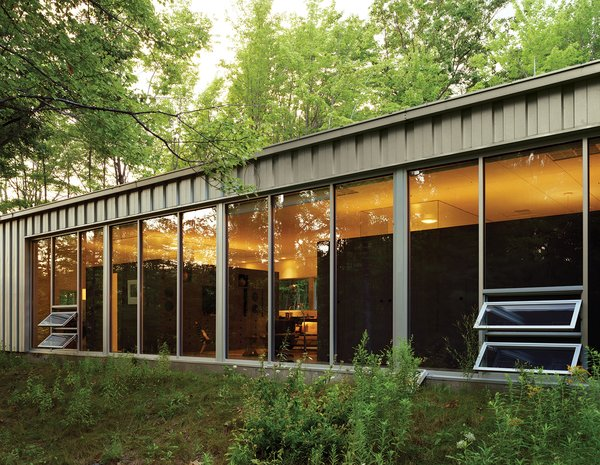 """Floor-to-ceiling windows capture natural light and warmth while offering expansive views of the woods to the south. """"In the winter, I like to use the house as therapy because there's so much light,"""" Cook says."""