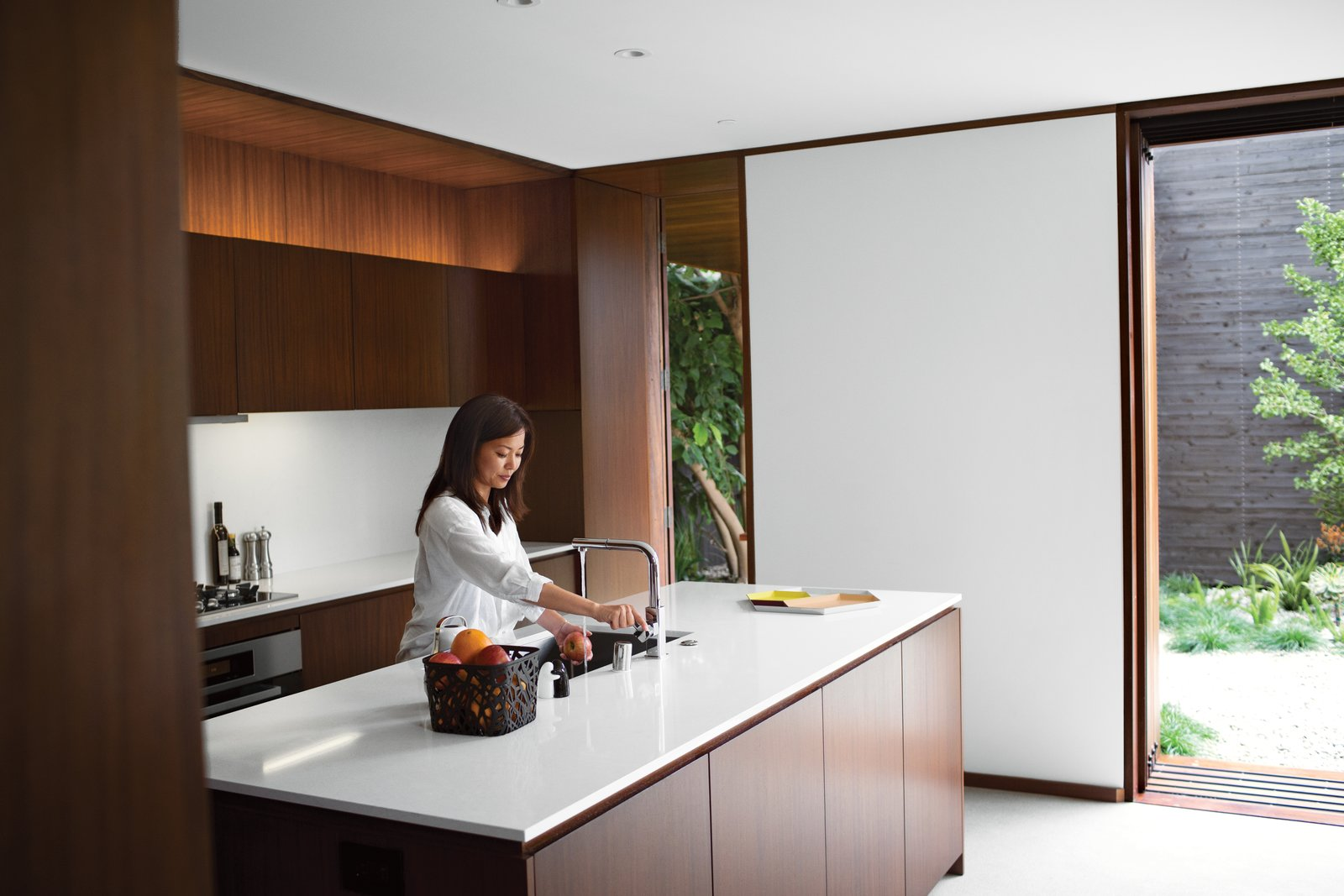 """I love the house more each day,"" says Tamami Sylvester of her and husband Michael's home by Sebastian Mariscal in Venice, California. The kitchen, which includes all Miele appliances, is sheathed in custom woodwork from Semihandmade. Accessories from A+R complement the Caesarstone countertops and Franke faucet. A LifeSource Water System provides filtration. Photo by Coral von Zumwalt.  Photo 4 of 10 in A Modern Bungalow in Venice Beach"