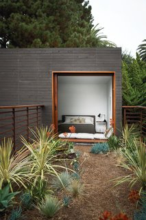 "A guest bedroom, with furniture from Room & Board, overlooks the bridge above the dining courtyard. The home's landscape architecture is by Ventura, California–based Jack Kiesel, and Mariscal was fully onboard with a program that respected the site's natural vegetation. ""Sebastian had an immediate reaction to the trees on the site,"" says the homeowner. ""There were several mature trees: a 40-foot-high pine tree, a California live oak, and a magnolia. So Sebastian immediately said—actually announced—that he was going to keep all the trees on the site."" Photo by Coral von Zumwalt."
