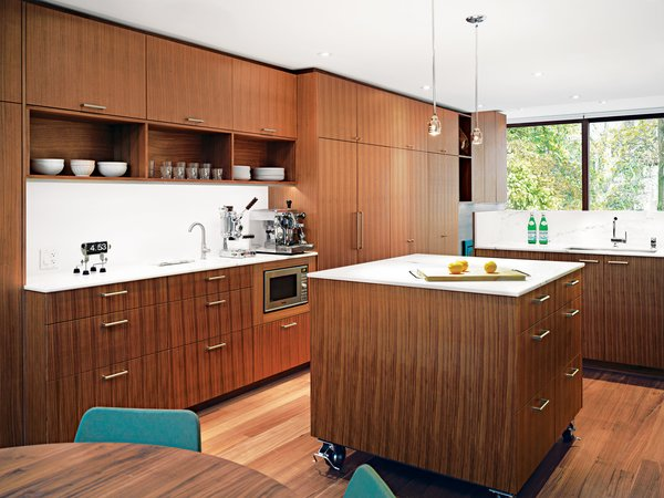 A movable island, set on stainless steel casters, sits in the center of the kitchen. The Panasonic microwave is built into the cabinetry and the August pendant lights illuminating the island are by Uberhaus.