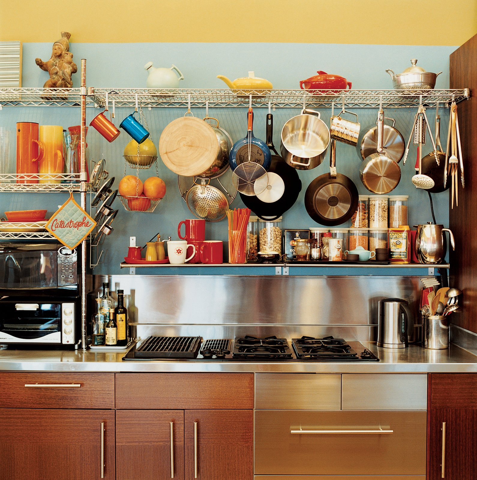 Vintage kettles and a wide-ranging assortment of pots and pans sit above kitchen cabinets from IKEA.