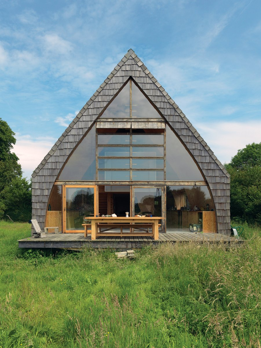 """I didn't want the kind of manicured garden that would mean I'd have to come out on weekends and mow the lawn,"" says Jean-Baptiste Barache of the French country home he built, mostly by himself, over a year and a half. The result: a house that looks like it's just been dropped into a field, casual, with nary a path leading up to it and a front door that can barely be detected on the red-cedar-shingled facade."