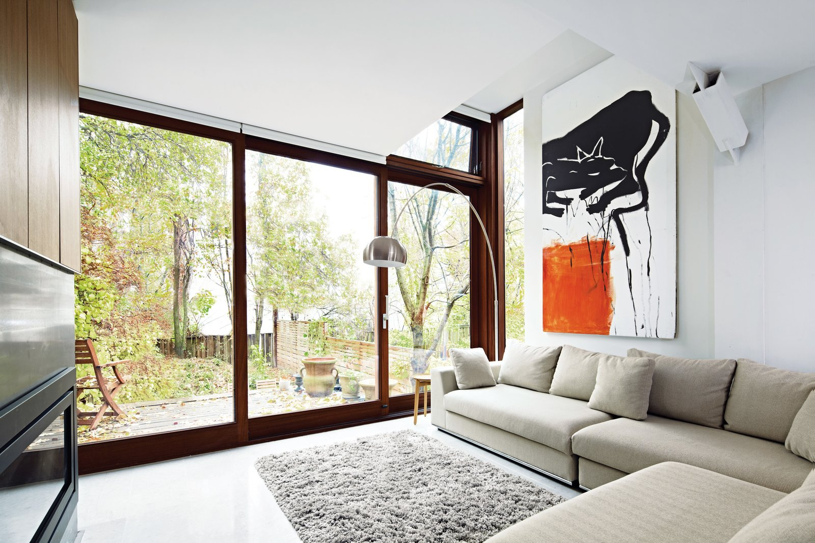 A sliding door by Bauhaus Fine Windows and Doors leads from the addition into the backyard. A sectional and floor lamp purchased from local shop Structube, Ikea rug, and Plaisir table by Formstelle for Zeitraum outfit the living room. Artist Rebecca Rodgers created the abstract painting.