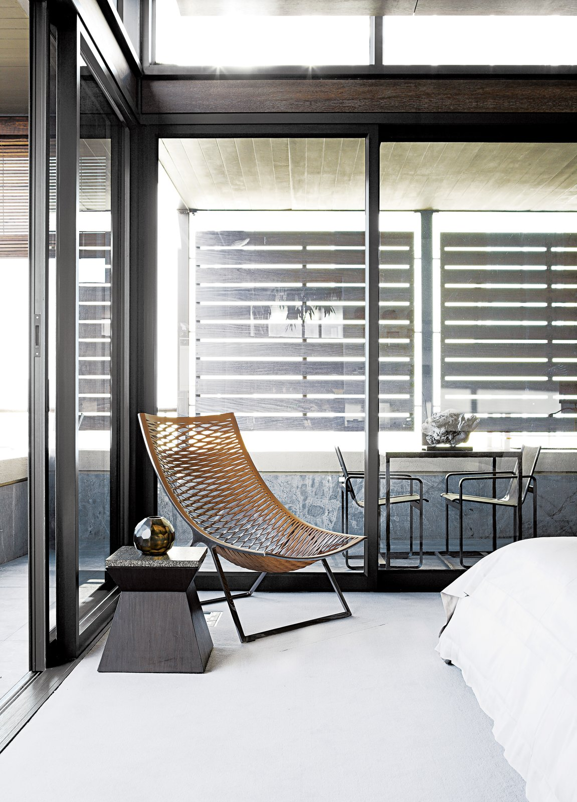 "In the master bedroom, a woven Loom chair by Matteograssi is paired with a wood-and-marble side table from Cécile & Boyd's. Sliding glass doors lead to the screened outdoor veranda with a custom bronze table and Neutra Batyline chairs from Marlanteak. ""The outside-inside flow was important to us, as the apartment is all about views and using the veranda spaces,"" says designer Geordi De Sousa Costa.  Bedrooms by Dwell from A Sophisticated Penthouse in Cape Town"