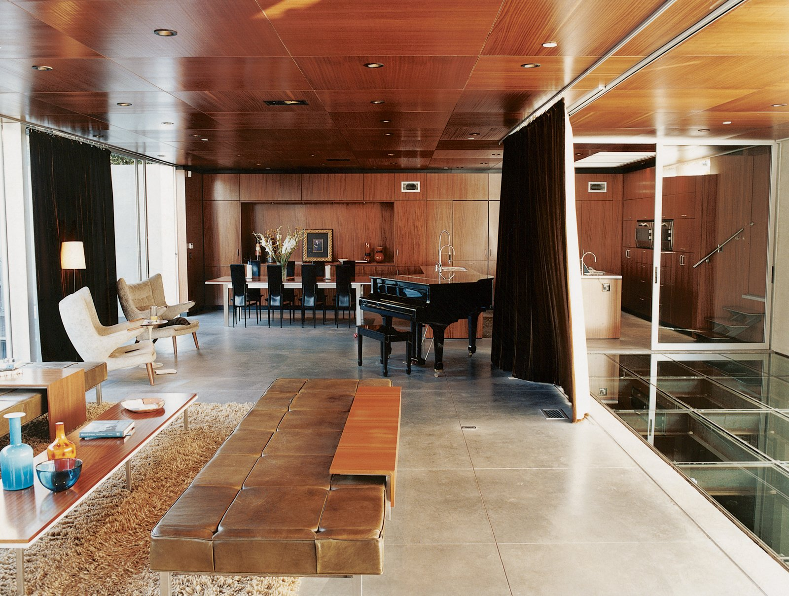In the humidor-like living room, modern classics like the off-white armchairs by Hans Wegner complement pieces of Segal's own design, such as the coffee table and long leather seating. The Jonathan - Photo 6 of 10