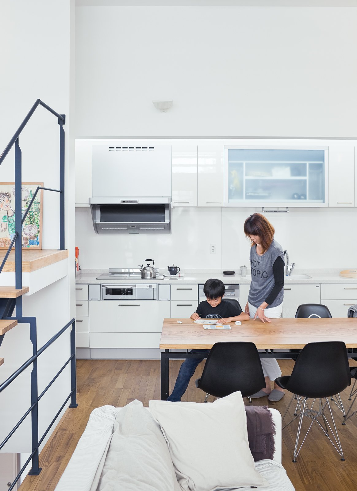 """Called the """"LDK,"""" for living, dining, and kitchen, the space is flexible—a blend of Western loft life and traditional Japanese homes, where rooms are multipurpose. Tagged: White Cabinet, Dining Room, Chair, and Table.  Photo 5 of 14 in Small Box Home with Black Metal Facade in Japan"""