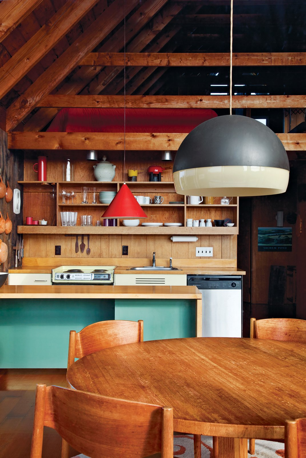 Jens Risom's family retreat in Rhode Island is a pitched prefab with a second-story loft. A no-frills kitchen features wooden shelves that mimic the home's beams. Photo by Floto + Warner. Tagged: Dining Room, Table, Pendant Lighting, Chair, Bar, and Medium Hardwood Floor.  Best Photos from Jens Risom's Block Island Family Retreat