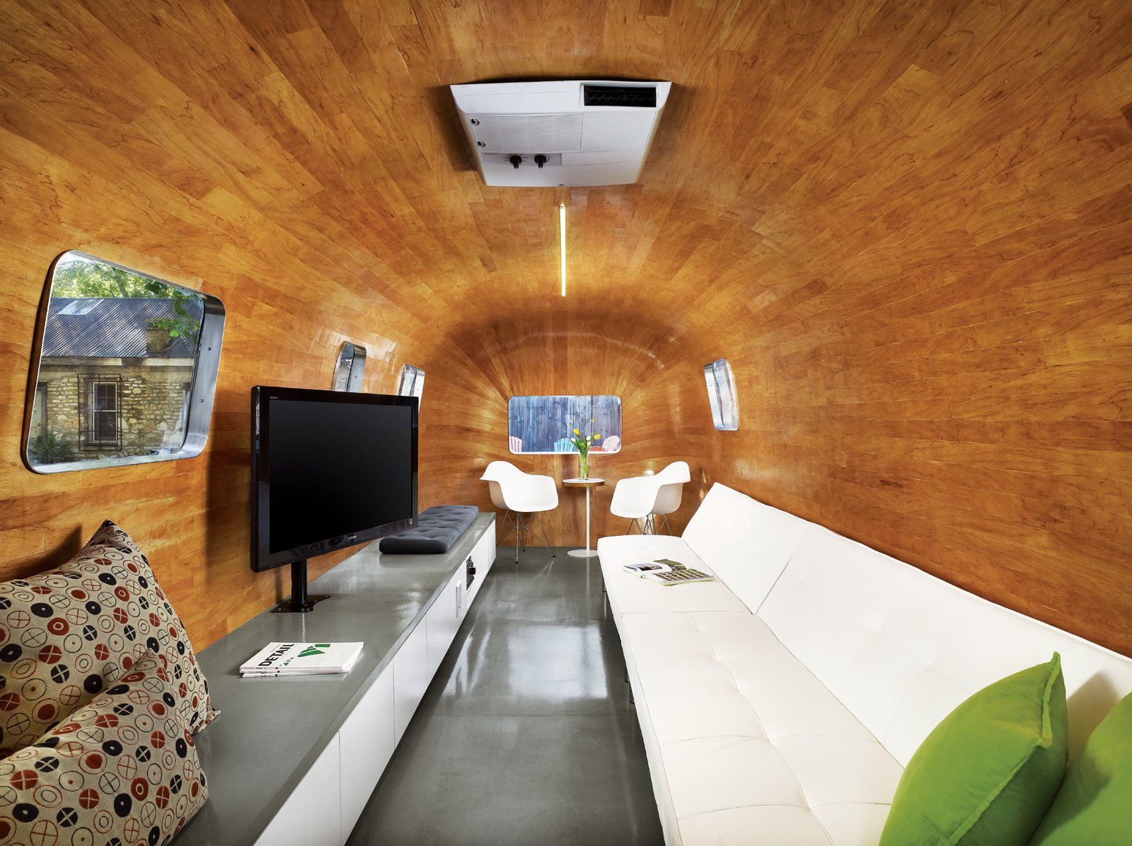 "The long sofa, bar, and television were obvious choices for a pre-show hangout, but how to achieve the continuous curve of the revamped Airstream's interior was not. Baldridge and his team labored to find a kind of wood that would accept the serious bend before hitting on mahogany veneer. As for the new entry, he imagined it as a ""modern I Dream of Genie bottle."""