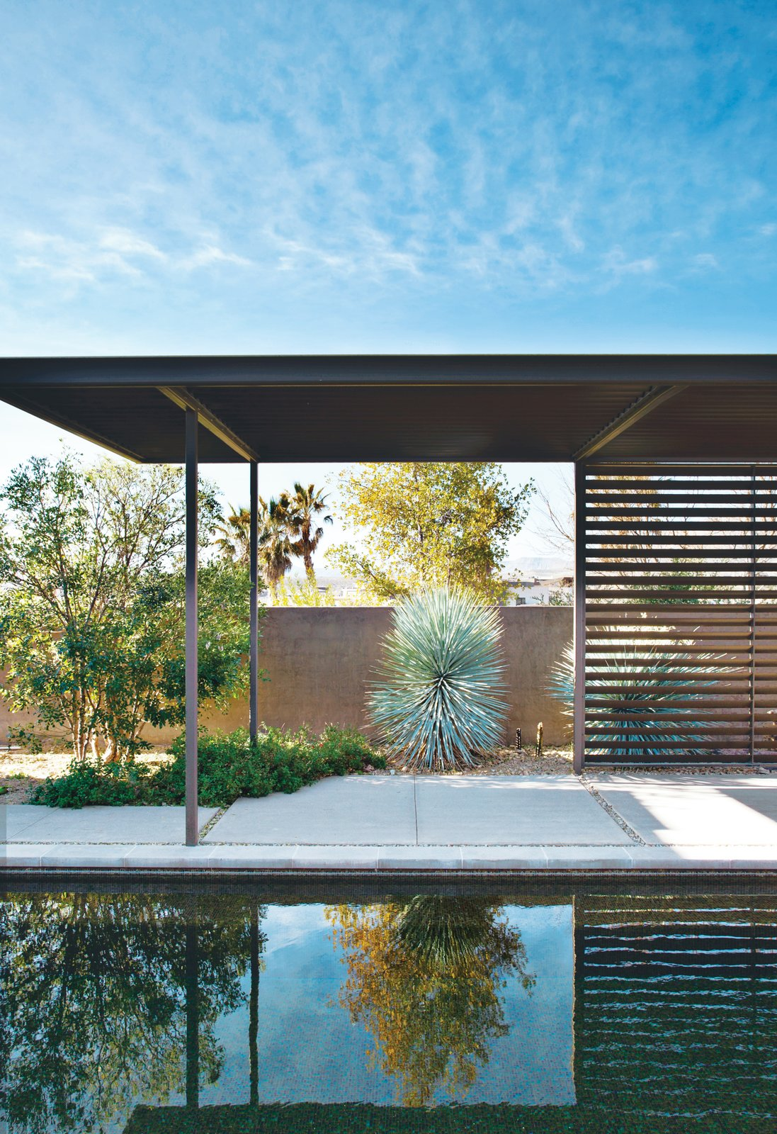 """Murren chose maintenance-free materials, such as Stepstone precast concrete pavers for exterior decks and river-rock-covered flat roofs. He recalls his neighbors' astonishment and delight when """"we went from a giant hole in the ground to a two-story house in just four days.""""  Prefab Homes by Dwell from A Picturesque Desert Prefab"""