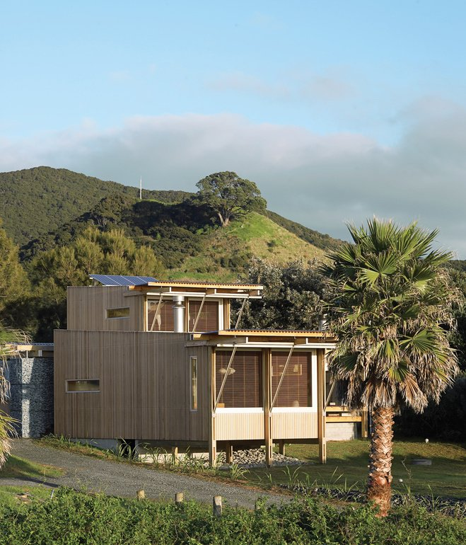 On New Zealand's Great Barrier Island, two architects designed a petite holiday home that takes care of its own water, electricity, and sewage needs.  Small Spaces in Rural Places by Kate Santos