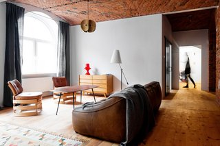 10 Remarkable Warehouse-to-Home Transformations - Photo 4 of 10 - By burnishing historic details and adjusting the floor plan, multidisciplinary studio Loft Szczecin restored and transformed a loft in a warehouse that dates from before World War II. The living room rug is a Polish textile from the 1930s.