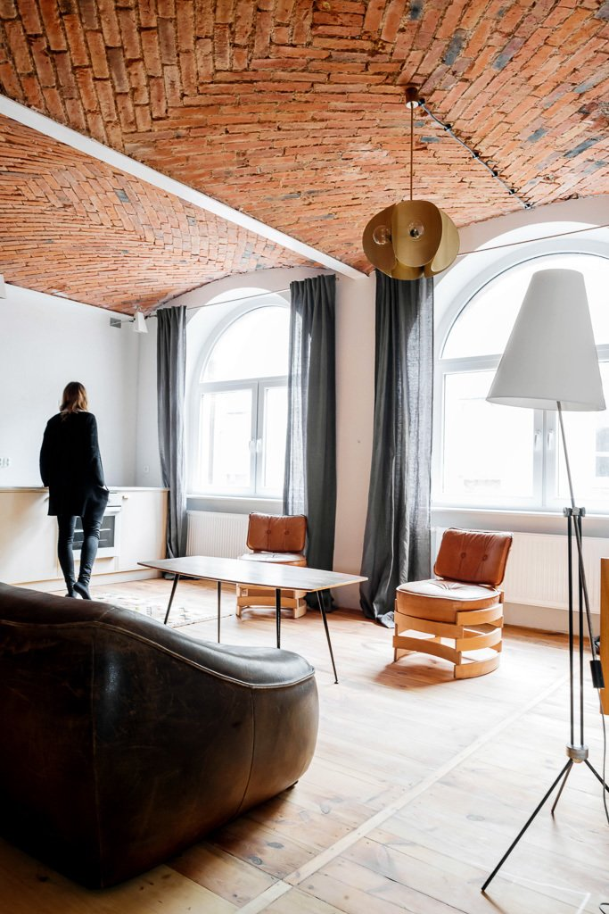 Much of the 1950s and '60s furniture collection comes from Denmark, the Czech Republic, Poland and the Netherlands. Tagged: Living Room, Sofa, Chair, and Pendant Lighting.  Photo 11 of 11 in 10 Charming Brick Interiors from These Days This Warehouse-Turned-Loft in Poland Stores a Stockpile of Cool, Vintage Furniture