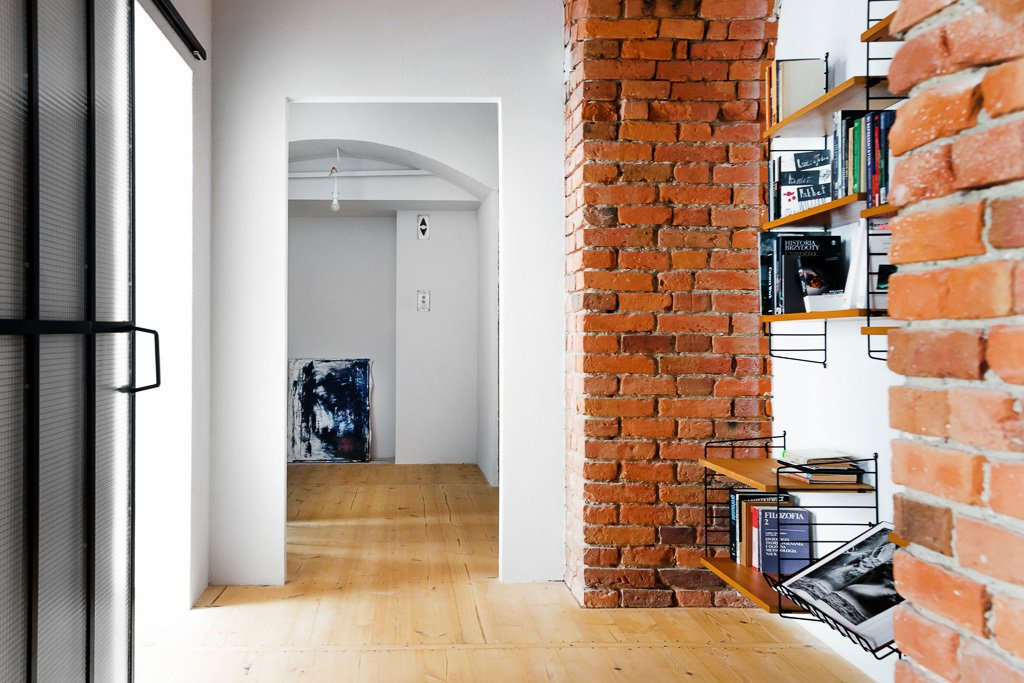 In addition to reconstructing an open living room, Loft Szczecin had to subdivide four smaller spaces to create privacy in the expansive warehouse. Tagged: Hallway and Light Hardwood Floor.  Loft by Kirill Egorov from These Days This Warehouse-Turned-Loft in Poland Stores a Stockpile of Cool, Vintage Furniture