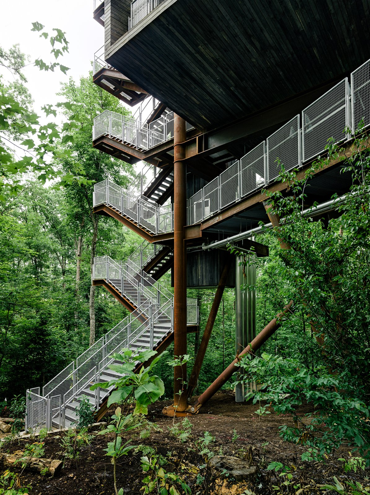 Mithun designed the tree house so that it would tread lightly on the land. The firm originally considered prefabricating the entire structure offsite but, in the research process, concluded that craning large modules into place would potentially harm the canopy. A combination of a bolted-together prefab structure and site-built wood housing yielded the least intrusive construction option.   The Summit Bechtel Reserve is located in West Virginia's coal mining country. The architects looked to the local structures—bridges, mining apparatus, and other industrial buildings—to inform the tree house's design. A 166-ton Cor-Ten steel megastructure supports the 125-foot-tall building. The use of regionally appropriate materials, like steel and black locust wood, was important to the architects. Tagged: Exterior and Treehouse Building Type.  Sustainability Treehouse by Diana Budds