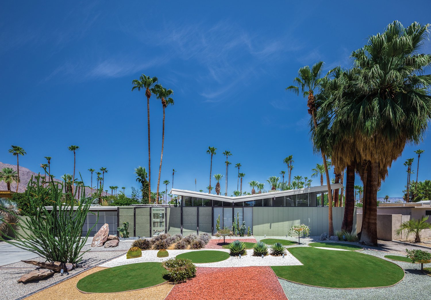 Krisel was also known for his boldly modern approach to landscape. The Menrad residence, shown here, features a distinct geometric design. The architect, working in the harsh Palm Springs climate, relied on hardscape elements—setting a precedent for drought-tolerant landscape design. Tagged: Exterior, Mid-Century Building Type, House, and Butterfly RoofLine.  A Crash Course in Palm Springs Architecture by Matthew Keeshin from Midcentury Lovers: You Can Thank This Architect for Transforming Palm Springs Into a Modernist Hotbed