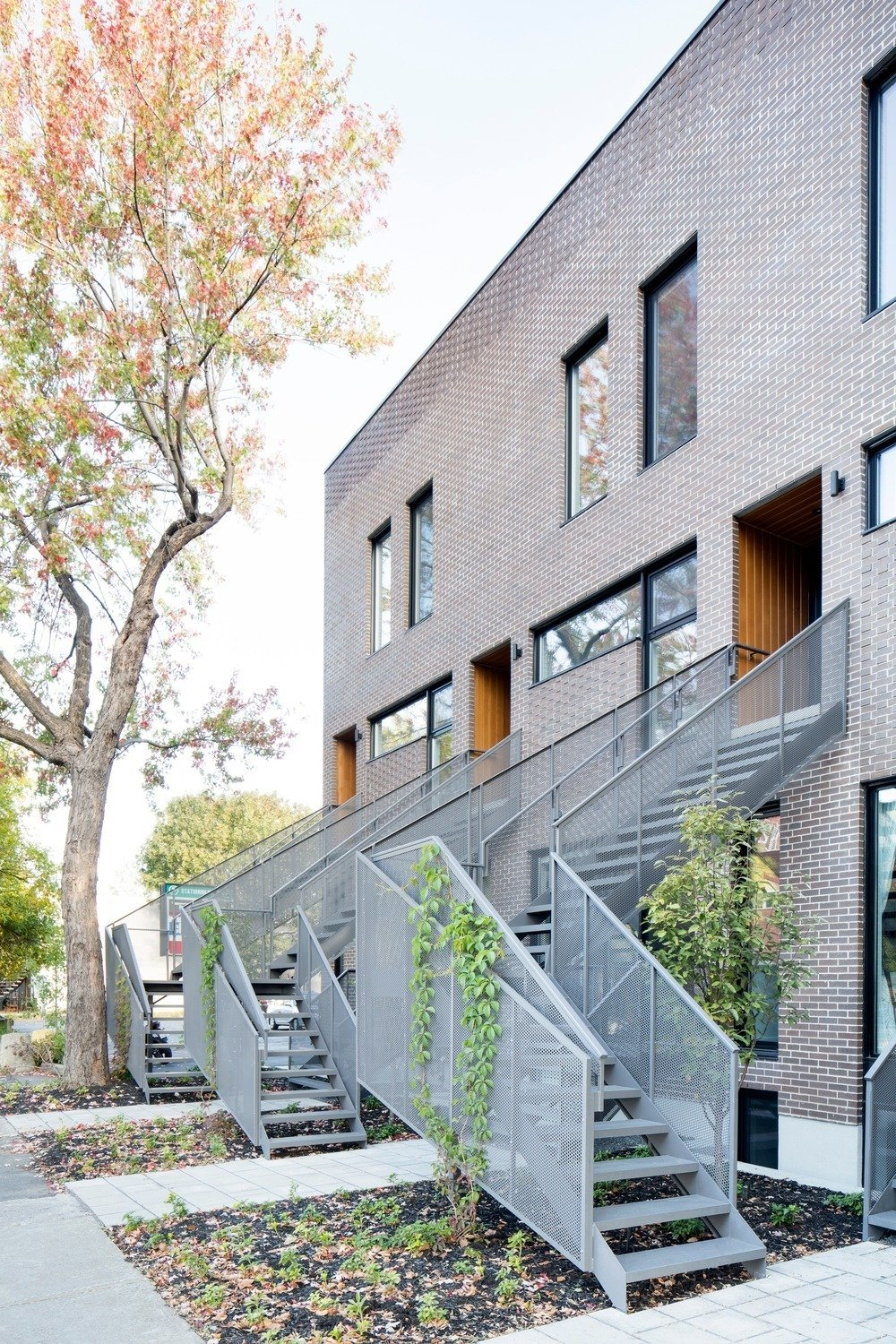 Plants wrap around the perforated aluminum railings for a natural touch. Tagged: Exterior and Brick Siding Material.  Best Photos from Meet Your New Neighbors: Minimal Town Houses with Character