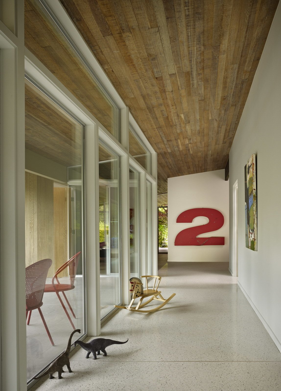 A bank of cabinets was replaced with a wall of glass, flooding the main hall with natural light and opening it to the courtyard. The vintage number 2 was salvaged from a theater marquee.  Midcentury Homes by Dwell from Midcentury Renovations We Love