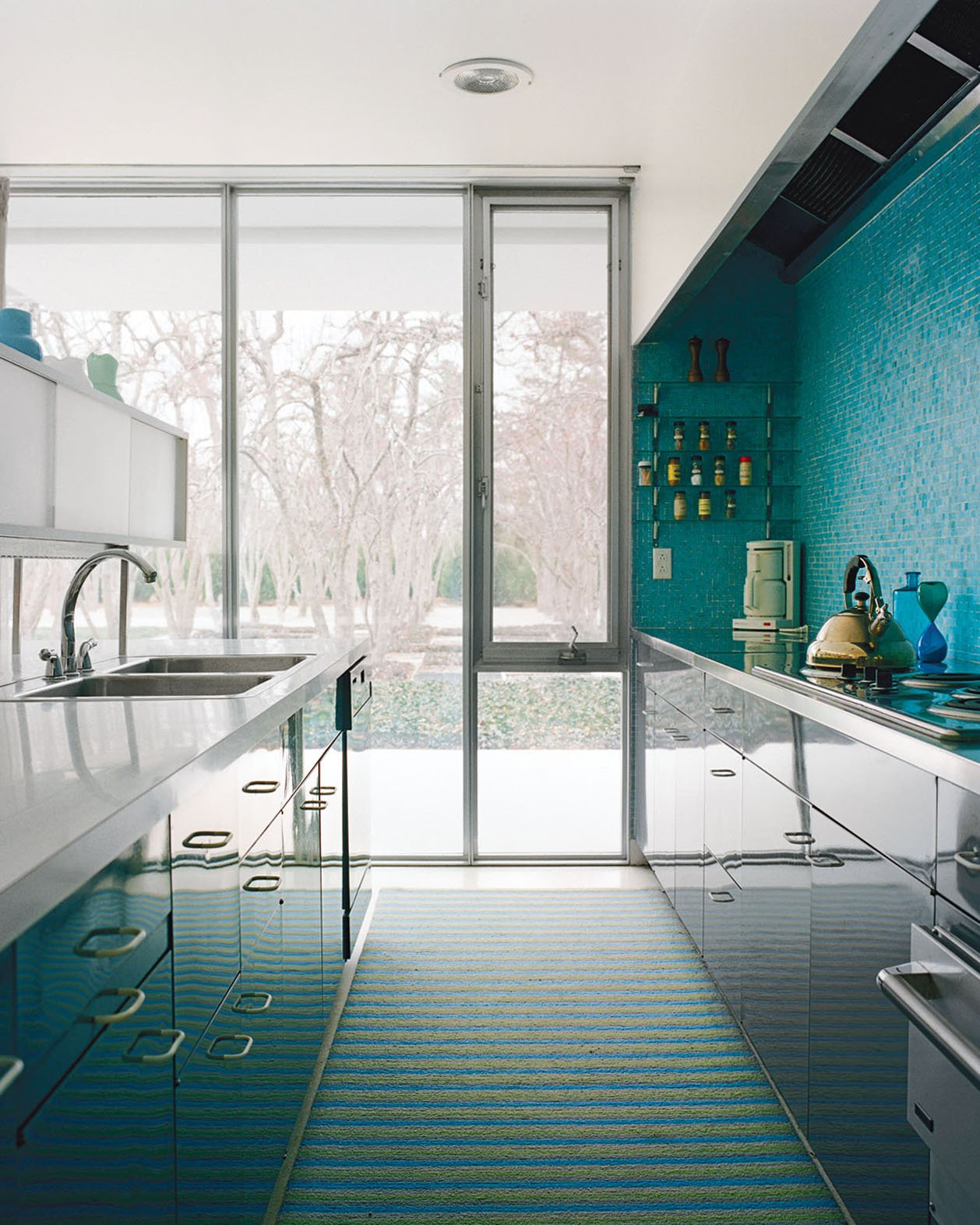 A mosaic tile wall softens the laboratory-like effect of the glossy kitchen cabinets.  Photo 2 of 12 in How the Colors in Your Kitchen Affect Your Appetite from Midcentury Renovations We Love