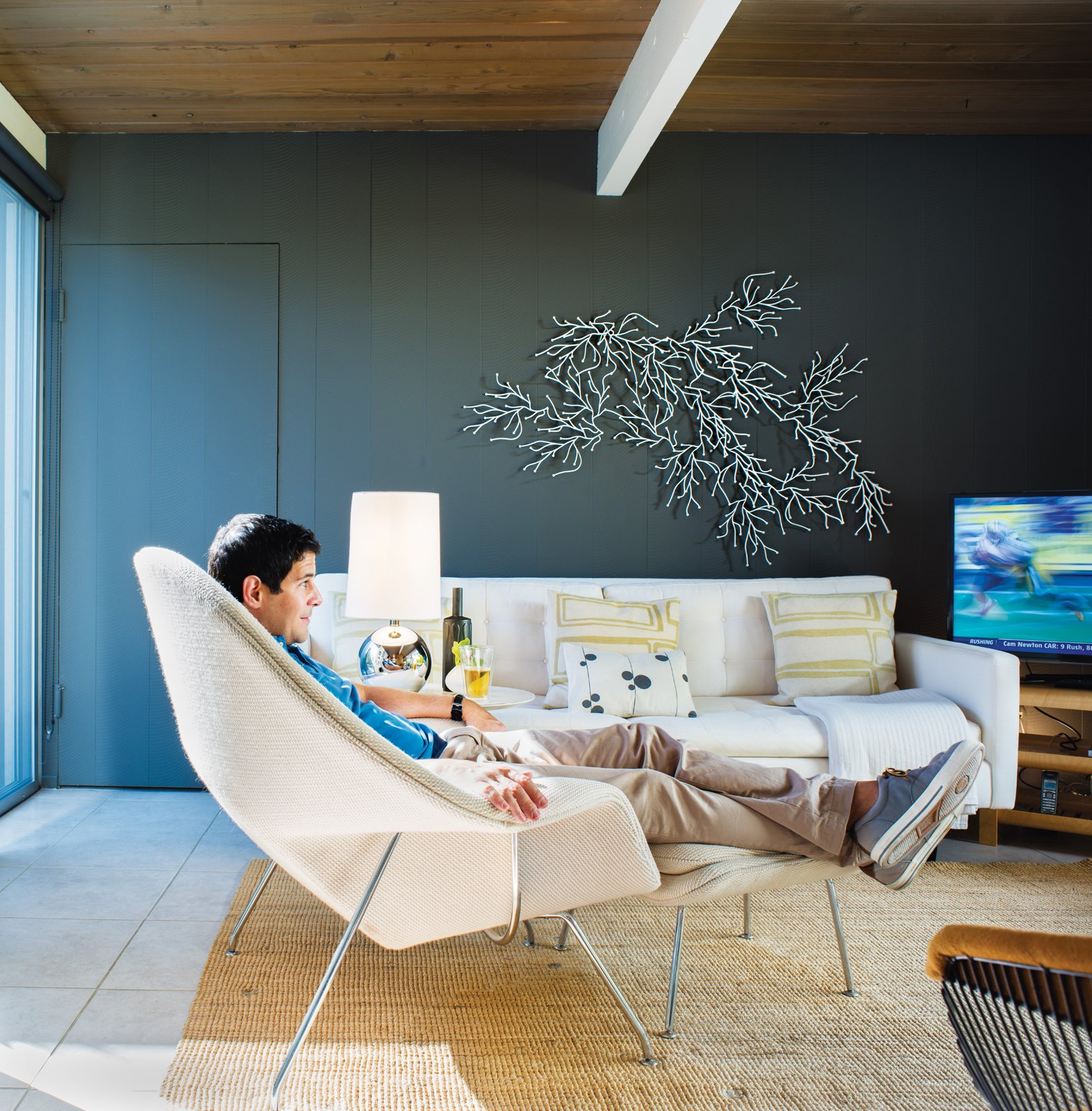 """See for Yourself  After painting the sitting room room Kendall Charcoal from Benjamin Moore's Aura line, Neely wanted a sculptural element that would show up against the dark hue. So he assembled his white Algues set, designed by the Bouroullec brothers for Vitra, on the wall behind the sofa with pillow by Judy Ross. """"Though the Bouroullec piece is manufactured in mass quantities, you can create your own take on it,"""" he says. """"It looks great no matter how you place it. I think of it almost like an inkblot—the randomness is part of its beauty.""""  Midcentury Homes by Dwell from Modern Furniture Fit for a Classic Eichler"""