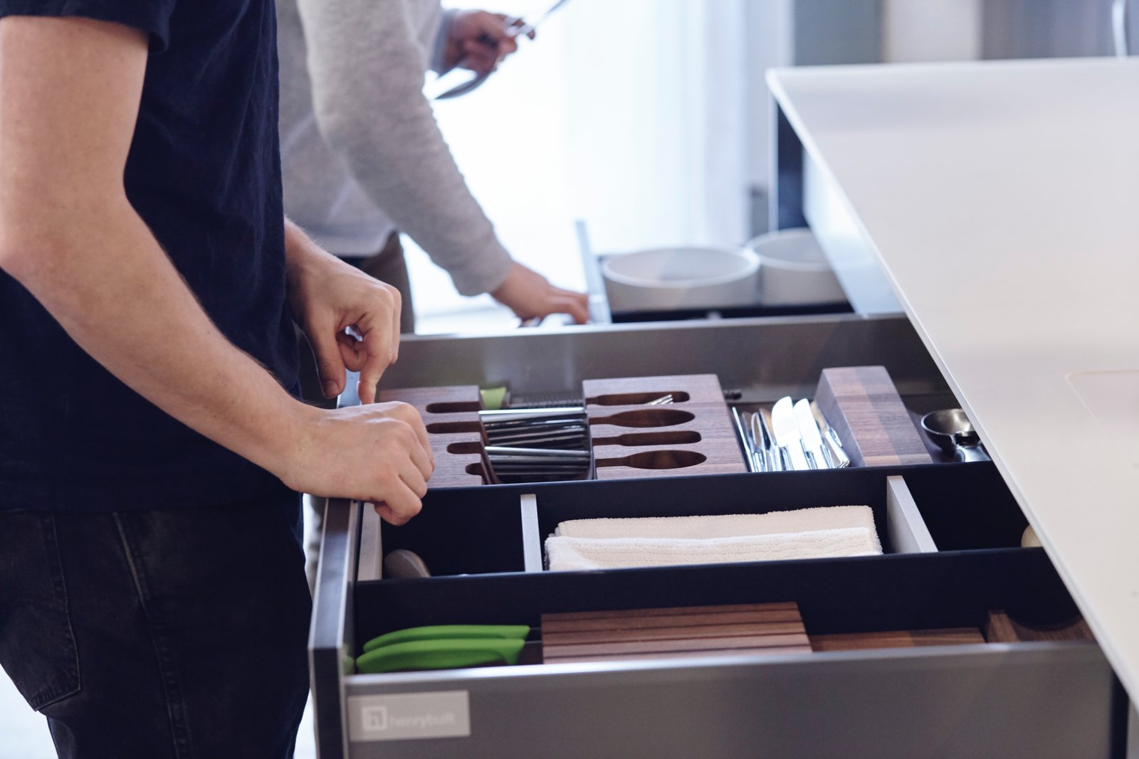 Their systems include award-winning components like the Drawer Accessory System, shown here with a construction of Paperstone and solid surface acrylic—both materials traditionally used in countertops. This addition extends high-performance function to the interior of a system, where users actually interact with it the most. As homeowners' needs evolve, they can arrange the reconfigurable dividers in any way they desire. The pieces simply snap back together, thanks to a number of small magnets that are carefully embedded.  Photo 5 of 8 in What Goes On Behind-the-Scenes at Henrybuilt's Seattle Test Kitchen
