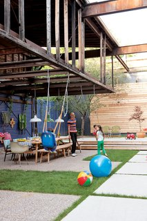 The courtyard is an extension of the house, with a big table that hosts parties, a stage for impromptu performances, and part of an old loft overhead that will one day become a treehouse for the children. Photo by Stacey Brandford.