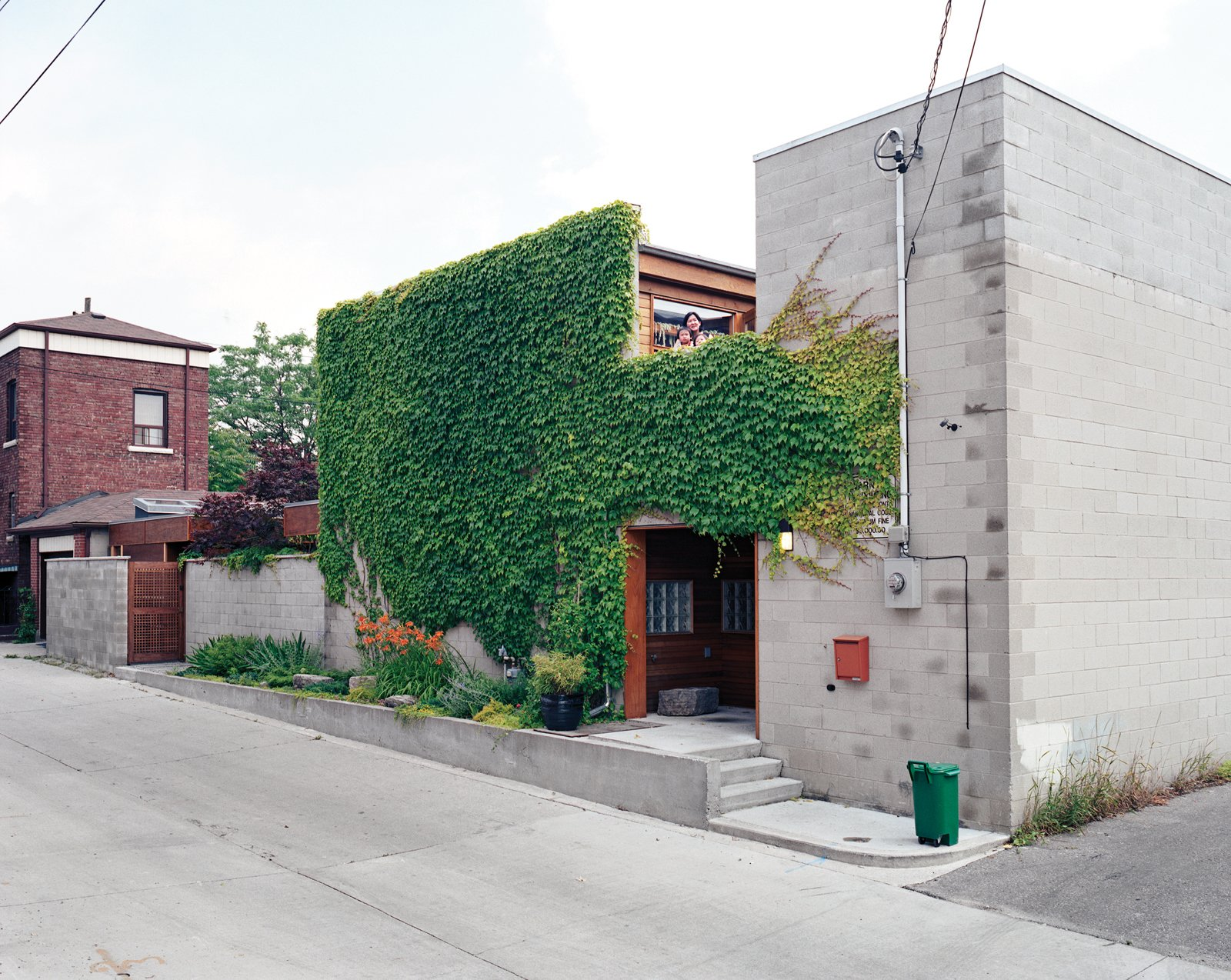 A narrow garden and climbing ivy soften and brighten the house's blank front facade.  Photo 17 of 17 in Inside Job