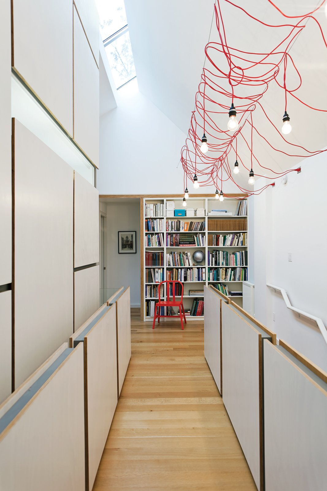 A dim Toronto Tudor gets an airy new look. The home's second-story hallway, which serves as an open office and library, was suffering from a severe lack of light. Lifting up one side of the old pitched roof made room for a linear skylight, which faces south to allow in as many rays as possible, and the modification transformed the top floor into a loftlike double-height space. Inexpensive detailing then added texture and scale: Simple plywood panels attached to cold-rolled-steel frames serve as guards along the stairs. Tagged: Hallway and Light Hardwood Floor.  Top Renovation Tips from the Pages of Dwell by Kelsey Keith from Toronto's 10 Top Homes