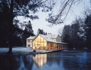 Hope Floats - Photo 5 of 12 - The Floating Farmhouse's semitransparent addition has a roofline that matches the pitch of the original 1820s farmhouse. A porch, tucked under the side eaves, is cantilevered over a stream that runs through the property. Ikea loungers are illuminated from the interior by commercial gymnasium lights repurposed as pendant lamps.