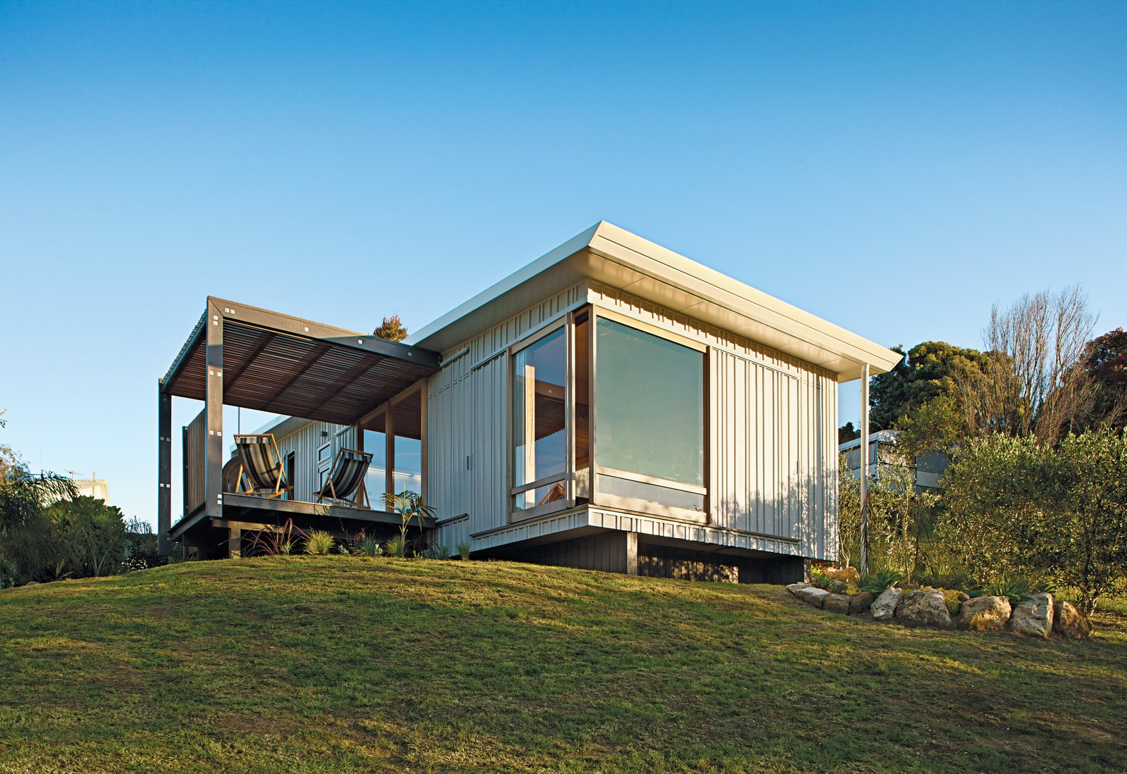 A compact prefab vacation home in the seaside community of Onemana Beach is clad in plywood and vertical timber battens finished in Resene's Lumbersider paint in Foam. Tagged: Exterior, Wood Siding Material, House, Prefab Building Type, and Flat RoofLine.  Photo 2 of 7 in A Compact Prefab Vacation Home