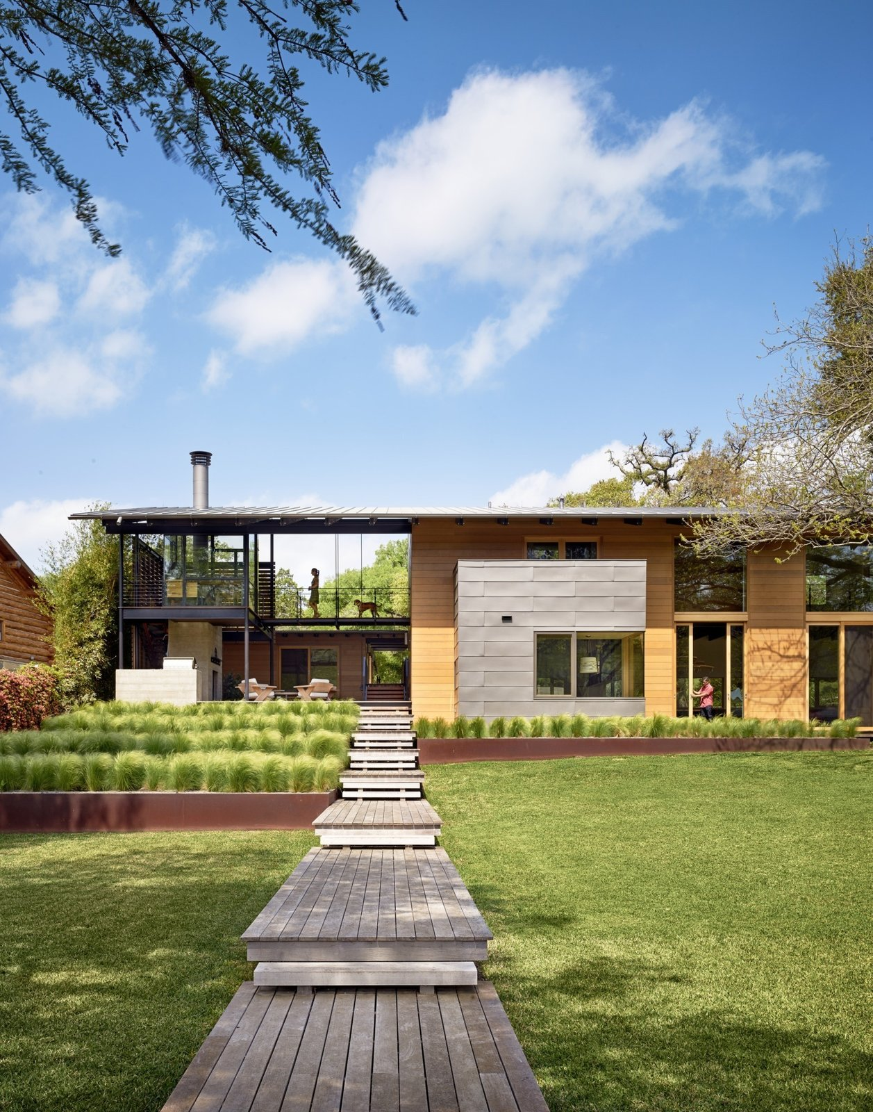 """""""Consistent with the lakefront cabin charm, the owners liked the idea of accessing much of the house from outdoor porches and walkways,"""" says architect Ted Flato. Supplies from Dynamic Architectural Windows and Doors bring light in to the home's covered spaces. Tagged: Exterior, House, Flat RoofLine, and Wood Siding Material.  Hog Pen Creek by Kelly Dawson"""