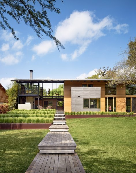 """Consistent with the lakefront cabin charm, the owners liked the idea of accessing much of the house from outdoor porches and walkways,"" says architect Ted Flato. Supplies from Dynamic Architectural Windows and Doors bring light in to the home's covered spaces. Photo  of Hog Pen Creek modern home"