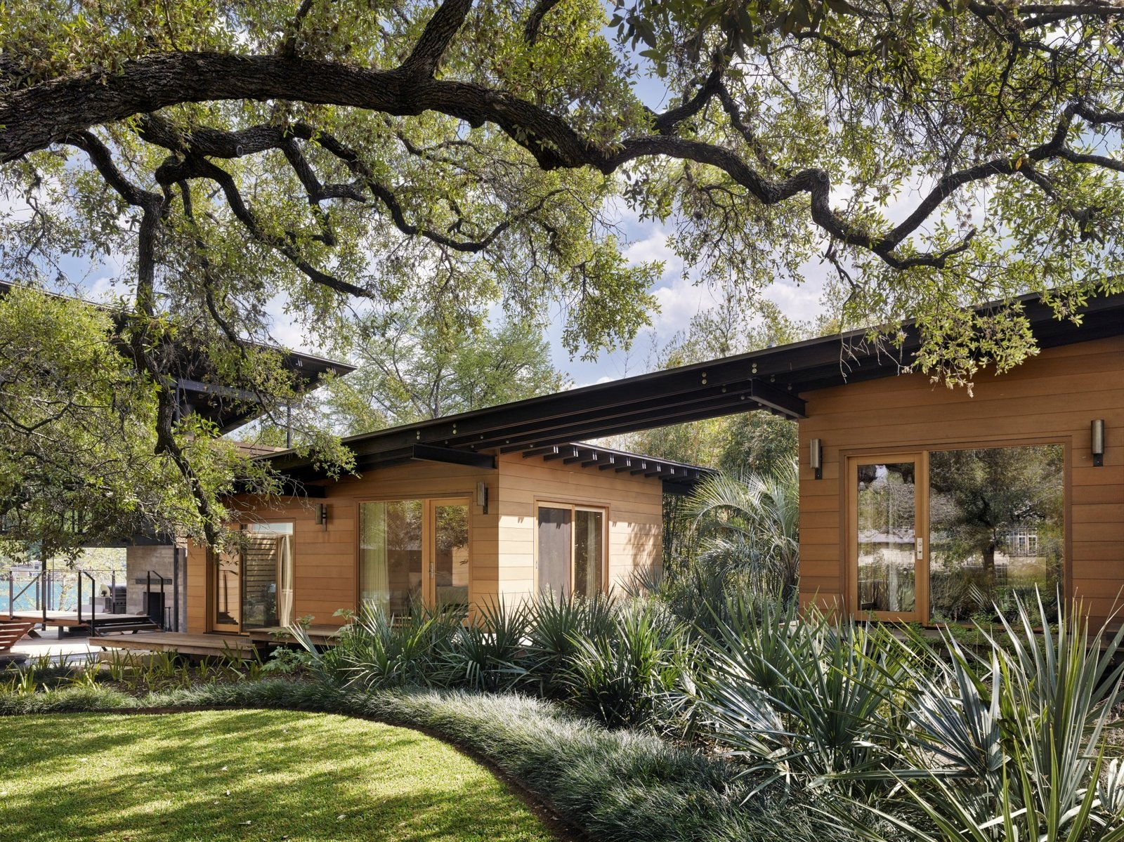 Porches and rolling glass doors draw in the river breeze to keep the home cool. Tagged: Exterior, House, Wood Siding Material, and Flat RoofLine.  Hog Pen Creek by Kelly Dawson