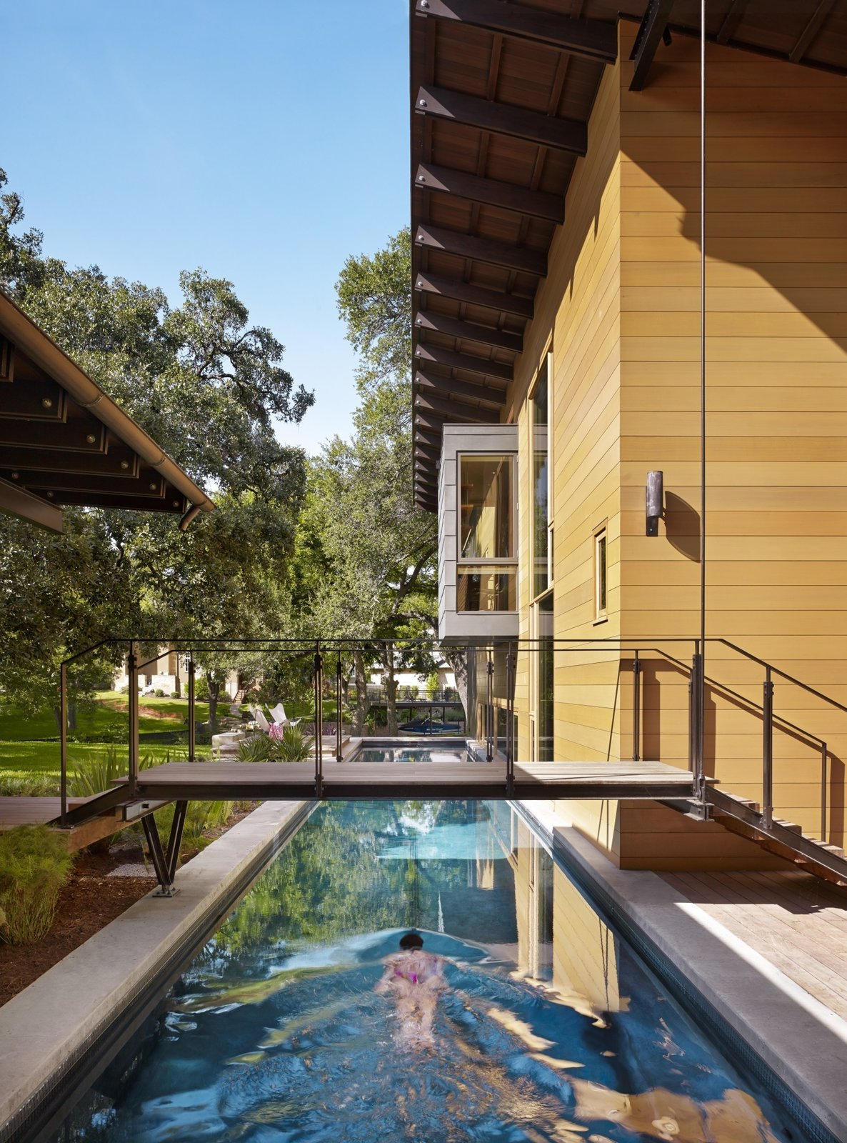 """""""The owners envisioned a place that engaged with the outdoors while providing accommodating spaces for their off-season training for triathlons,"""" Flato notes. A 75-foot-long lap pool on the west end of the home comes in handy during practice."""