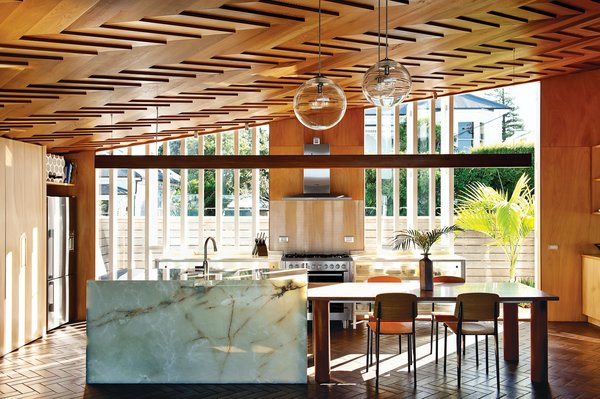 """In the kitchen, the showstopping ceiling's herringbone pattern is echoed by the terra-cotta tiles on the floor. Architect Michael O'Sullivan, who designed the steel-and-glass kitchen cabinets, the table, and the pendant lights (made by Lava Glass), further amped up the richness of the room by specifying an onyx kitchen island. Interior designer Yvette Jay, a collaborator and classmate of O'Sullivan, kept her material palette """"tight and limited. I had to restrict myself so that everything here ties in with the architecture."""""""