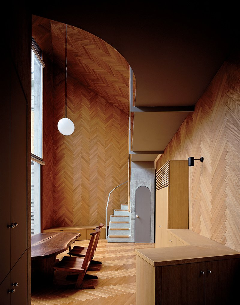 Masahiro and Mao Harada of Mount Fuji Architects Studio wanted to break with the traditional definition of a house when they designed this small Tokyo home. They achieved their goal by using the same material for the ceiling, the walls, and the floor, creating a space that flows beautifully.   Photo by Ryota Atarashi. Tagged: Living Room, Ceiling Lighting, Pendant Lighting, Chair, and Medium Hardwood Floor.  Composition by Lara Deam from Compact Wooden Home in Japan