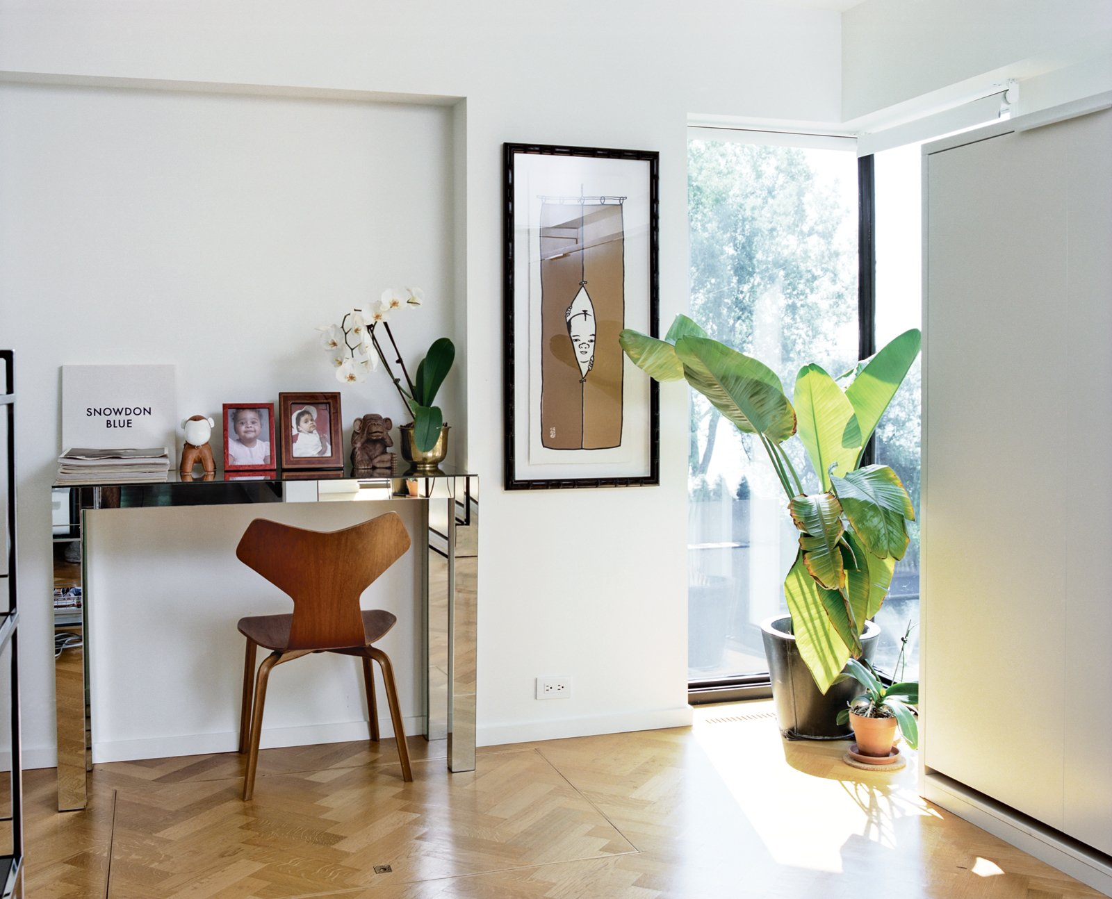 They restored small alcoves to rooms including the office (shown here) and living room and worked carefully with the existing windows. They also hunted down a craftsman, Marc Ablasou, to install oak floors in a herringbone pattern—a touch that subtly complicates Safdie's aesthetic. In the office, the mirrored console is vintage and the Grand Prix chair is by Arne Jacobsen for Fritz Hansen. Tagged: Living Room and Chair.  Photo 5 of 9 in A Renovated Flat in Moshe Safdie's Habitat '67