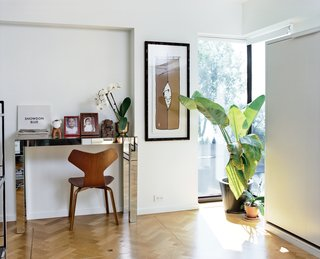 They restored small alcoves to rooms including the office (shown here) and living room and worked carefully with the existing windows. They also hunted down a craftsman, Marc Ablasou, to install oak floors in a herringbone pattern—a touch that subtly complicates Safdie's aesthetic. In the office, the mirrored console is vintage and the Grand Prix chair is by Arne Jacobsen for Fritz Hansen.