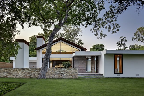The home's outer walls were dry-stacked with limestone cut from a Texas Granbury quarry, and its gabled roof was made with weathered Cor-Ten steel that emits the same maverick spirit as a Richard Serra sculpture. The freestanding fireplace just inside the courtyard was even salvaged from the old house's living room. Clean stucco walls contrast with the grass and trees, while reclaimed wood siding complement them. Photo  of Preston Hollow modern home