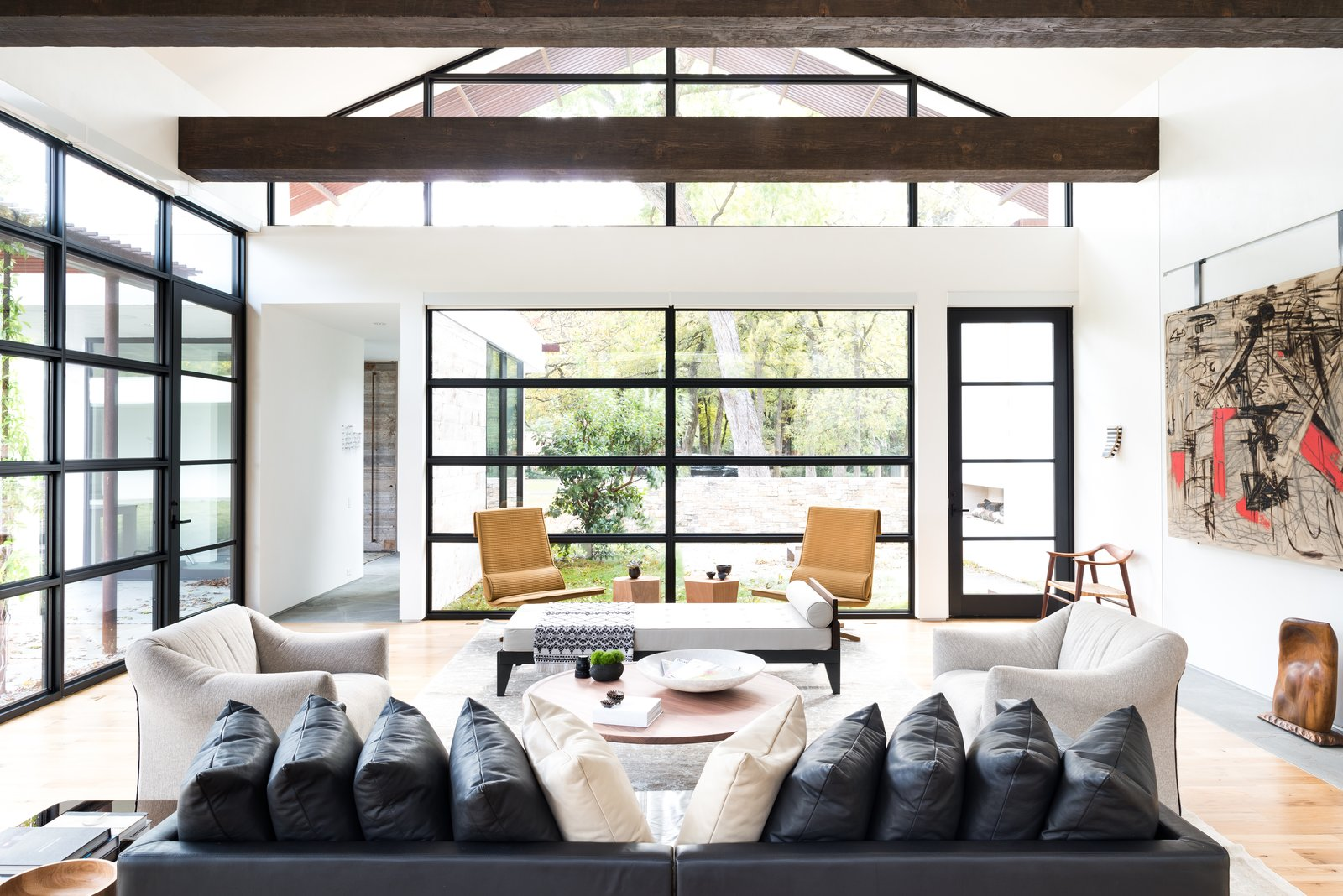 """For this project, the husband loved ultra-modern design, while the wife leaned towards a more traditional aesthetic. How to please both? """"Through the design process, we learned that their tastes were actually more closely aligned when we focused on the desired 'feel' of the home versus specific design details,"""" Field says.  He and his colleagues balanced rustic, exposed ceiling beams with elegant venetian plaster walls, and artful aluminum storefront windows with functional white oak plank flooring."""