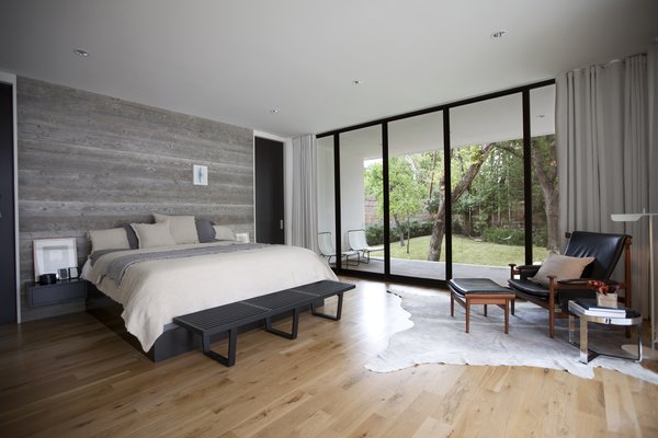 "In the master bedroom, the textural appeal of the reclaimed wood wall, bedding, and rug contrasts with the black leather of the African-inspired 'Bwana' Chair by Finn Juhl, which sits beside a 'TAB' reading lamp by Barber Osgerby. ""We believe a quality project is defined by the sum of all its parts versus any individual feature or design move,"" Field says. Photo 6 of Preston Hollow modern home"